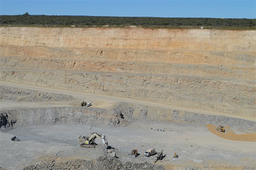 Photo 3. Otjikoto pit in Otjikoto gold mine: house-sized trucks demonstrate the sheer scale of the gold-bearing magnetic anomaly, which would not have been discovered without subsurface geophysics.