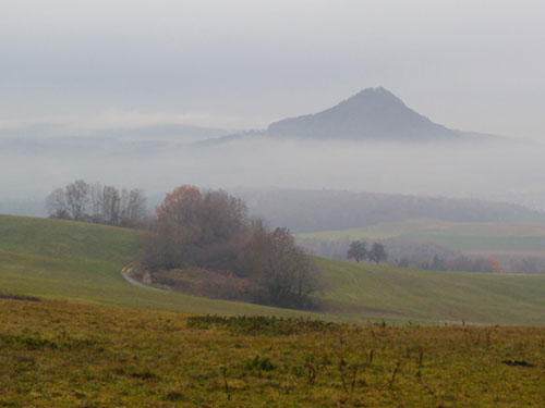 Figure 1. The first stop was a misty  overview looking towards the south with in the distance a suggestion of snowy crags – the Alps.