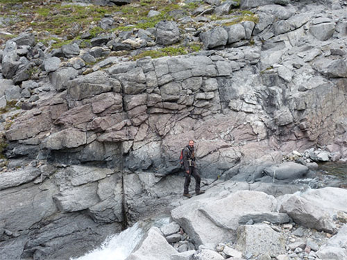 Gregor Markl for scale on magmatic layering in kakortokites, Ilímaussaq. Black layers are arfvedsonite-rich, red layers eudialyte-rich, and grey layers are alkali feldspar and nepheline-rich.