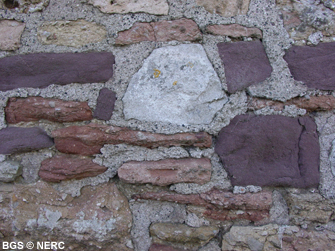 Examples of local buildings stones: blocks of grey Carboniferous Limestone, purple Portishead Formation and red Dolomitic Conglomerate. Rowberrow.