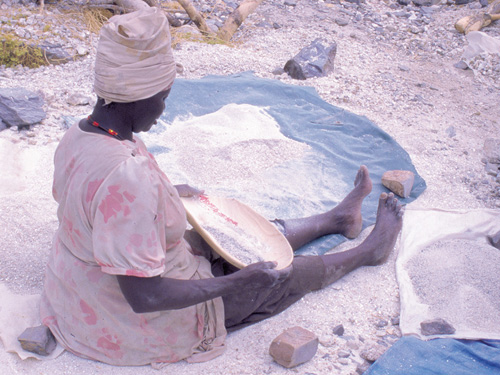 Artisanal miner separating tin-tantalum ore at the former Uis tin mine, Namibia BGS©NERC
