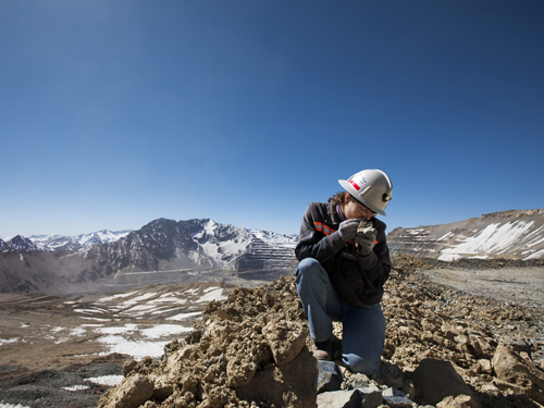 Exploration geologist examines copper bearing ore in the Chilean Andes, ©Anglo American