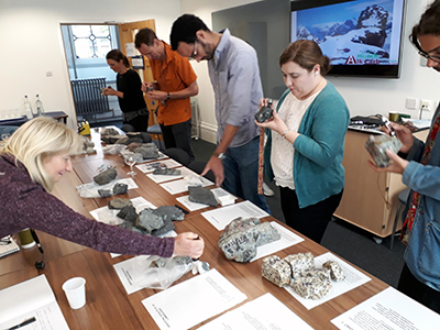 Participants 'hands on' session to learn about Ilímaussaq rocks.  Photo Copyright Adrian Finch.
