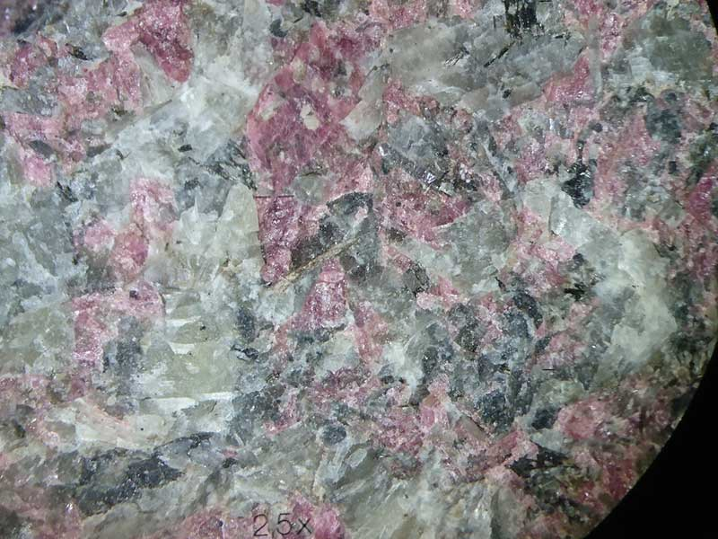 Light pink interstitial Mn-rich eudialyte from Poços de Caldas, in a matrix of feldspar and nepheline. Copyright Anouk Borst